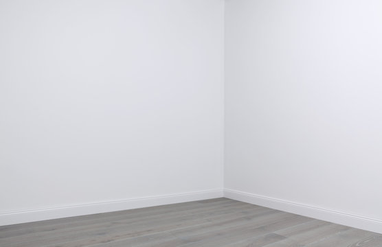 White walls and wooden flooring in the corner of empty room