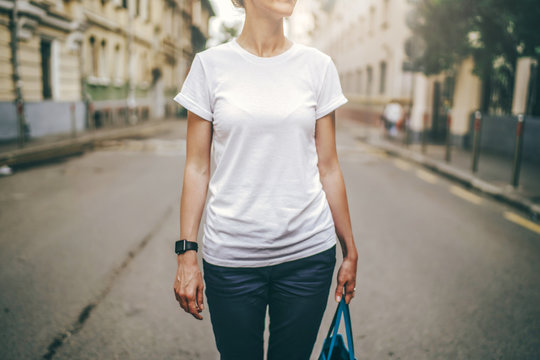 Front view. Cropped image. Summer day, a young woman in a white t-shirt standing on a city street. Wristwatch on the hand of the girl. Blurred background. Advertising space, mock up.