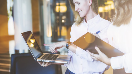 Teamwork, close-up laptop in hands of young businesswoman. Second woman is holding clipboard and making notes. Presentation of project. Girl uses gadget.
