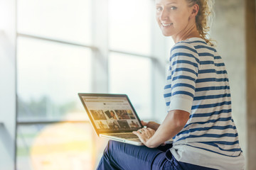 Rear view. Young smiling woman in striped T-shirt sitting and uses laptop. Girl browsing internet, chatting, blogging, checking email. Online shopping, learning. Window in soft focus on background.