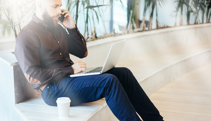 Side view. Young bearded businessman in brown shirt sitting and using laptop while talking on cell phone. Nearby stands cup of coffee. Man uses digital gadget. Guy chatting, blogging, checking email.