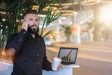 Fronte view. In left part of image young bearded businessman in brown shirt standing and talking on cellphone while holding cup of coffee. In background is laptop. Diagram on computer screen.