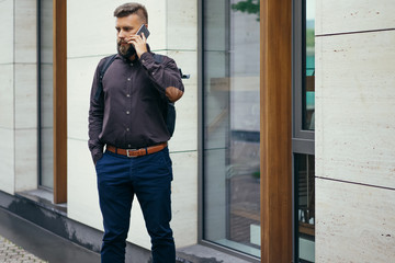 Young bearded businessman in a brown shirt with a backpack standing on a city street and talking on the cell phone. In the background is a modern building. Man using digital gadget.