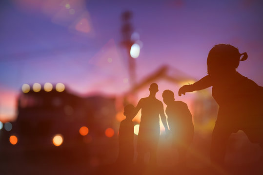 Silhouette of family four people worker., Mother-Father and the child with construction site background on sunset lighting., Family support worker concept