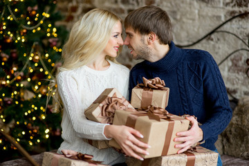 Happy couple of lovers in pullovers give each other gifts