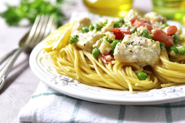 Codfish in a cream sauce with vegetables garnished with spaghett