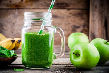 healthy green smoothie with banana, green apples, spinach and chia seeds in mason jar