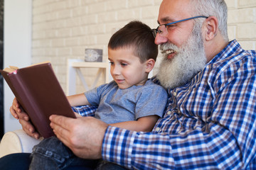 Grandfather supporting his kid to read a book while sitting in a