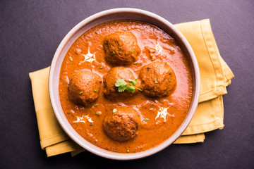 malai kofta curry - classic North Indian dish. vegetarian alternative to meatballs served with tandoori roti or indian bread and green salad, selective focus