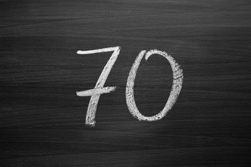 number seventy enumeration written with a chalk on the blackboard