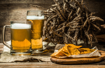 Beer in mug, glass with potato chips on board