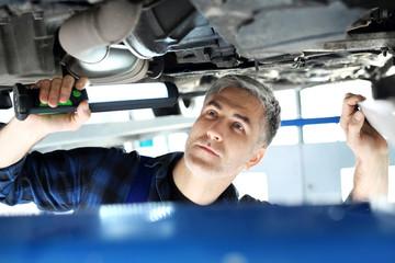 Warsztat samochodowy, mechanik naprawia samochód.