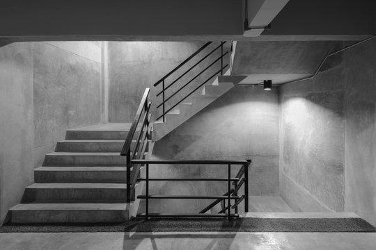 Empty modern rough concrete stairway with black steel handrail