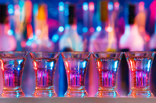 Five burning drinks in shot glasses on bar counter