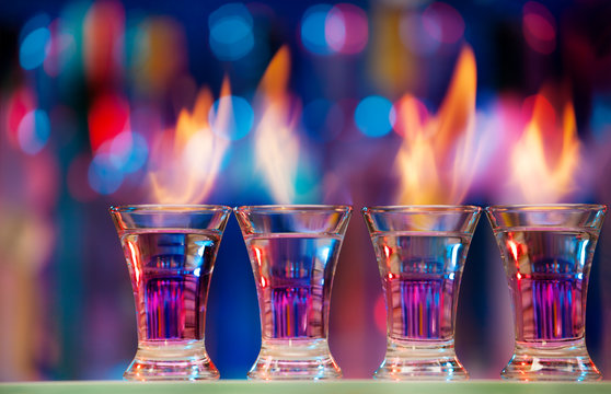 Four hot shot glasses on a bar counter