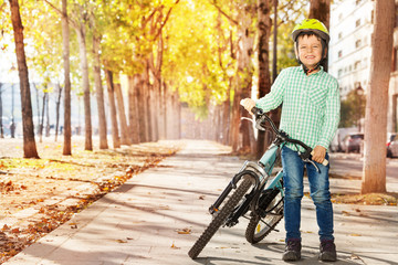 Boy in helmet standing with bike at autumn park