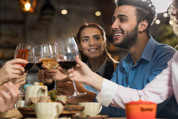 Young Business People Group Drink Wine Sitting Restaurant Table, Friends Hold Glasses Clink Toasting Smiling Mix Race Men Women