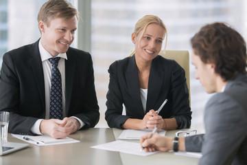 Businessman and businesswoman deceiving a client