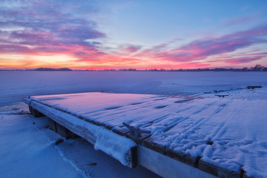 Winter Sunrise on a Snow covered Lake and Fishing Dock