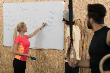 Sport Fitness People Group Write Results After Crossfit Training On Board, Young Healthy Man And Woman Gym Interior