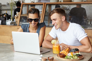 Two friends using laptop together, sitting at cafeteria. Young man wearing white t-shirt looking at screen of notebook pc with interested expression while stylish woman in shades showing him something