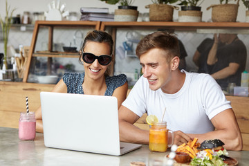 Beautiful couple watching videos online, sitting at cafe table with laptop, food and drinks, using free wireless internet connection, smiling, looking at screen while having lunch together on weekend