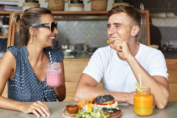 Handsome man in white t-shirt holding a French fry and telling good story to pretty woman in shades, both having cheerful looks, siting at cafe table with burger and fresh drinks. People and leisure