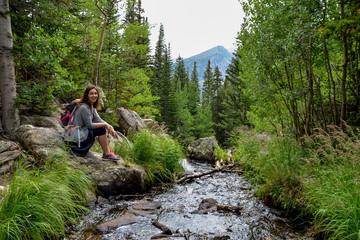 female hiker sitting near Tyndall Creek Emerald lake trail, Rocky Mountain National Park, Estes Park, Colorado, United States