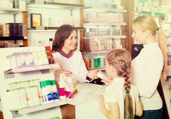 Happy woman pharmacist helping customers