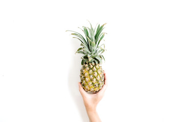 girl's hand holding pineapple. flat lat, top view