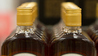 Top of plastic bottles with cognac or brandy standing in the liquor store. From the front.