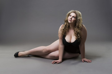 Young beautiful blonde plus size model with big natural breasts in underwear, xxl woman on gray studio background