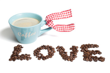 A blue cup of black coffee with foam and coffee beans spelling love on a white background