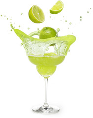 lime falling into a margarita cocktail splashing isolated on white