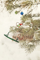 decorated Christmas tree in a snowy forest, sledges, blanket and