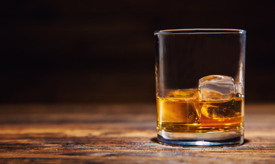 Glass of whiskey with ice cubes served on wood