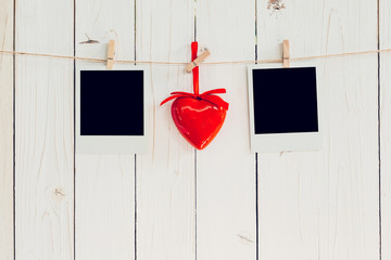 Two photo frame blank and red heart hanging on white wood with s