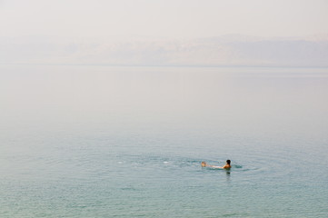 Man swimming in the Dead Sea, Jordan, Middle East