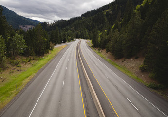 Interstate highway with four lanes and divider in lush Pacific Northwest USA setting.