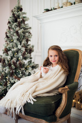 Little girl drinking milk near Christmas tree in morning at home