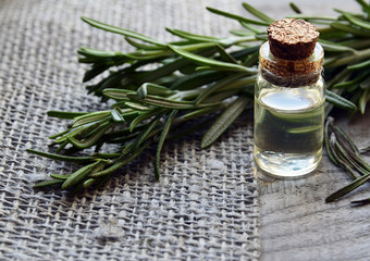 Rosemary essential oil in a glass bottle with fresh green rosemary herb on old wooden table.Rosemary oil for spa,aromatherapy and bodycare.Extract oil of rosemary.Selective focus.