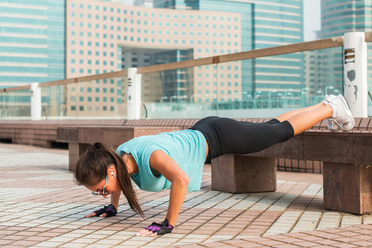Fitness woman doing feet elevated push-ups on a bench in the city. Sporty girl exercising outdoors