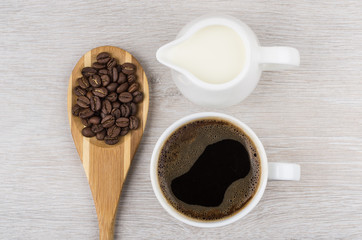 Coffee beans in wooden spoon, milk and cup of espresso