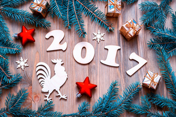 Happy New Year 2017 background with 2017 figures,Christmas toys, fir tree branches and rooster- New Year 2017 symbol