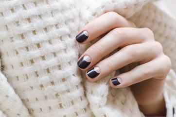Female hand with dark brown nail design.
