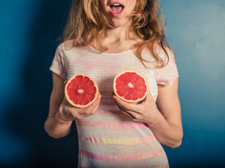 Young woman holding her grapefruits