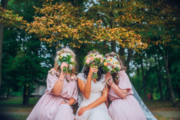 Wedding. The bride in a white dress standing and embracing bridesmaids in green and yellow garden...