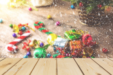 Wooden board empty table in front of  blurred snowing background of Christmas concept with pine cane, gift box, candy balls for mock up  display or montage your