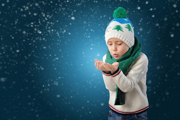 Portrait of a adorable toddler boy blowing snow in winter hat and scarf on blue background drawing snowflakes
