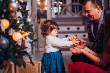 Portrait of affectionate family in christmas time. Family (mother, father, and little cute daughter) sitting near a Christmas tree and smiling face in the frame